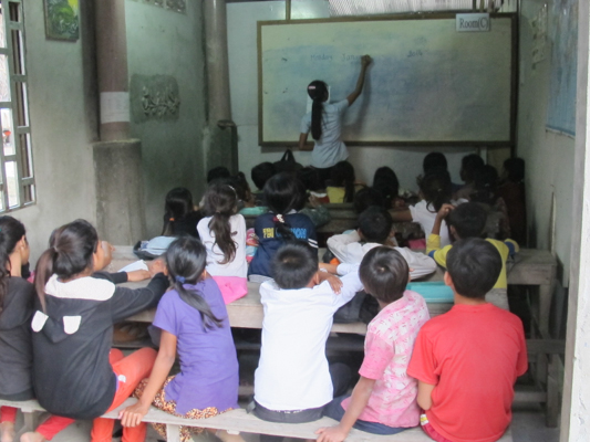 Students in an indoor classroom being taught by KCEO teacher Sokhi.